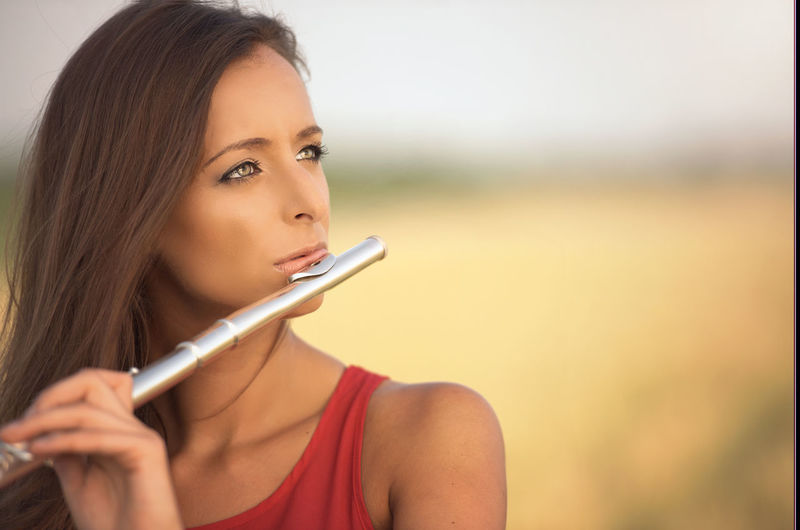 Close-Up Of Beautiful Woman Playing Flute Outdoors