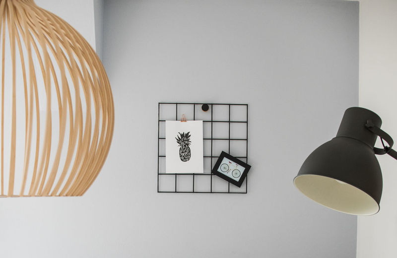 Close-up of electric lamp on table against wall at home