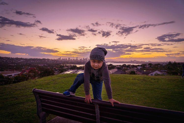 Portrait of smiling boy on landscape against sky during sunset