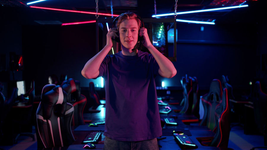 Portrait of young man standing in internet cafe