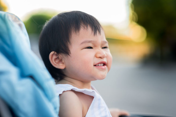 Smiling Baby Looking Away While Sitting In Carriage Outdoors