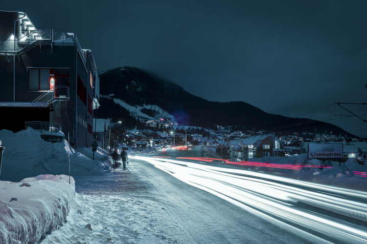 Architecture Beauty In Nature Building Exterior Cold Temperature High Street Illuminated Light Trail Long Exposure Motion Mountain Nature Night No People Outdoors Road Scenics Sky Snow The Way Forward Transportation Weather Winter Mobility In Mega Cities