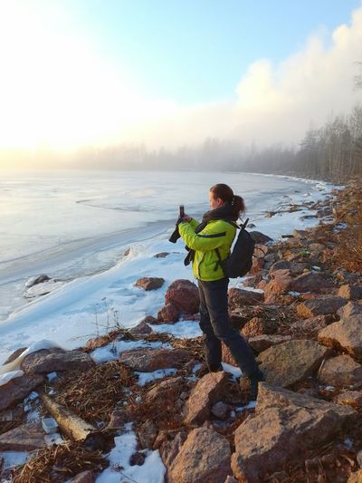 One Person Winter Outdoors Nature Warm Clothing Cold Temperature Snow Beauty In Nature Beach Outdoor Photography Finland Sea Nature Foggy Sunset Shades Of Nature Landscape Taking Picture Woman Portrait Beautiful Weather Water Halla Stones & Water Backpack Frozen Sea Mobile Conversations