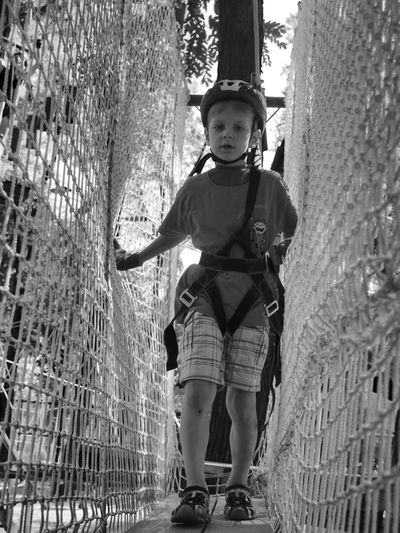 Boy playing on the bungee Black And White Boy Bungee Casual Clothing Caucasian Day Full Length Leisure Activity Lifestyles Looking At Camera Monochrome People And Places Person Playing Young Adult