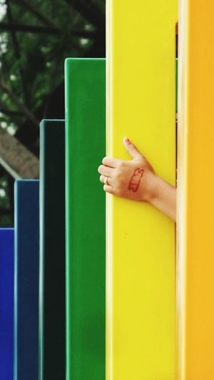 Cropped hand of woman amidst multi colored metal