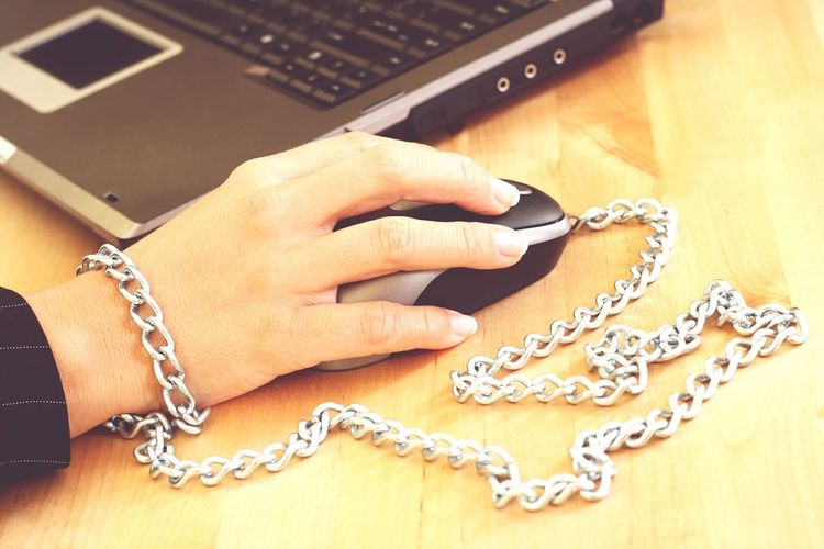Cropped Hand With Chain Using Laptop At Table