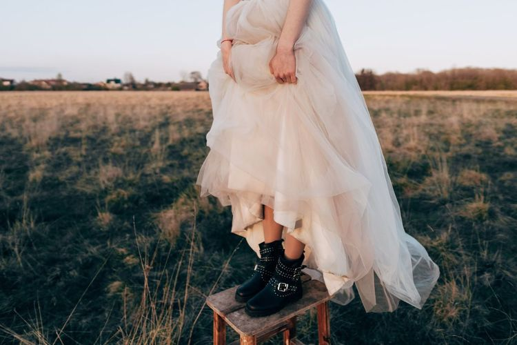 Low section of woman standing on stool over field