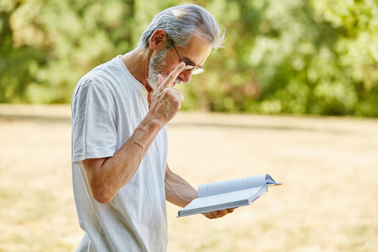 Man Reading Book While Standing On Field