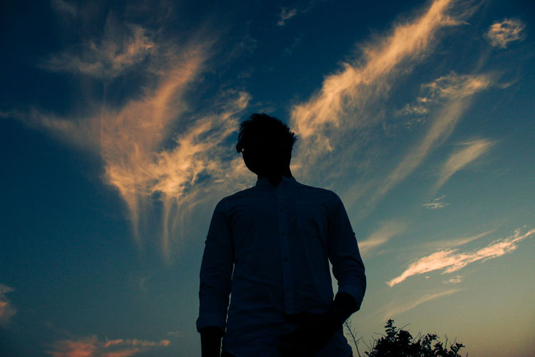 Rear view of silhouette man standing against sky during sunset