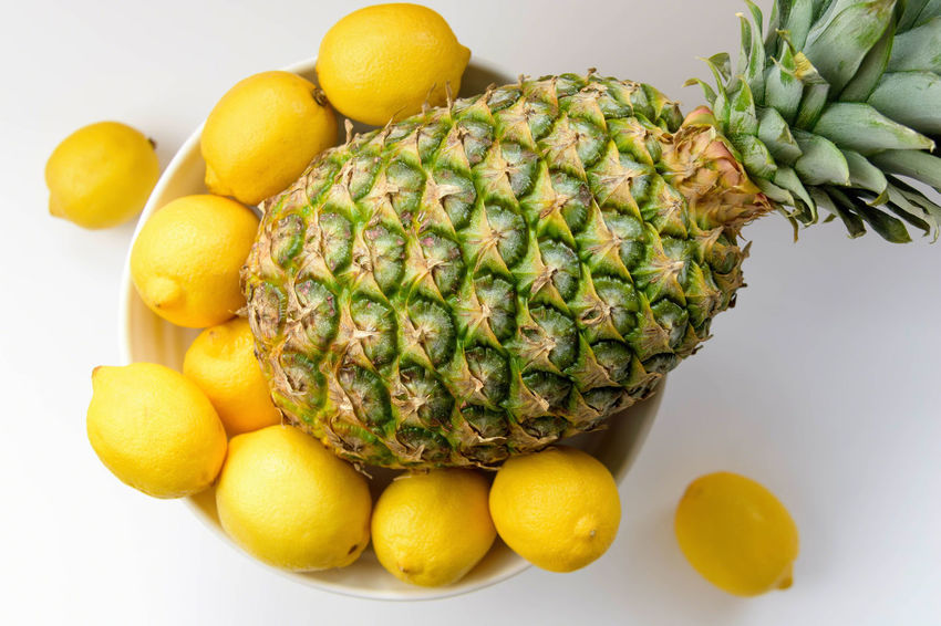 Healthy colorful fresh fruit bowl with pineapple and lemons Eating Freshness Green Pineapple Closeup Food Fresh Fruit Fruit Bowl Fruits Healthy Juicy Overhead Texture Tropical Yellow