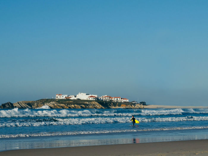 Mid distance view of man with surfboard walking in sea against clear sky