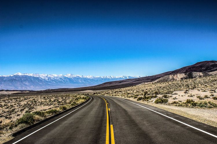 Empty Road By Mountains Against Clear Blue Sky