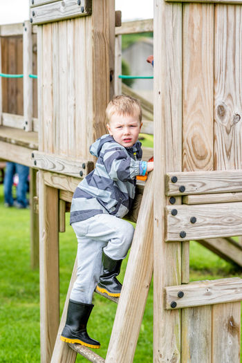 Day view of boy in playground summer park Blond Hair Boys Child Childhood Children Only Day Full Length Grass One Boy Only One Person Outdoors People Playground Playing Portrait Wood - Material