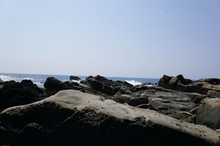 Scenic view of sea in front of rocks against clear sky on sunny day
