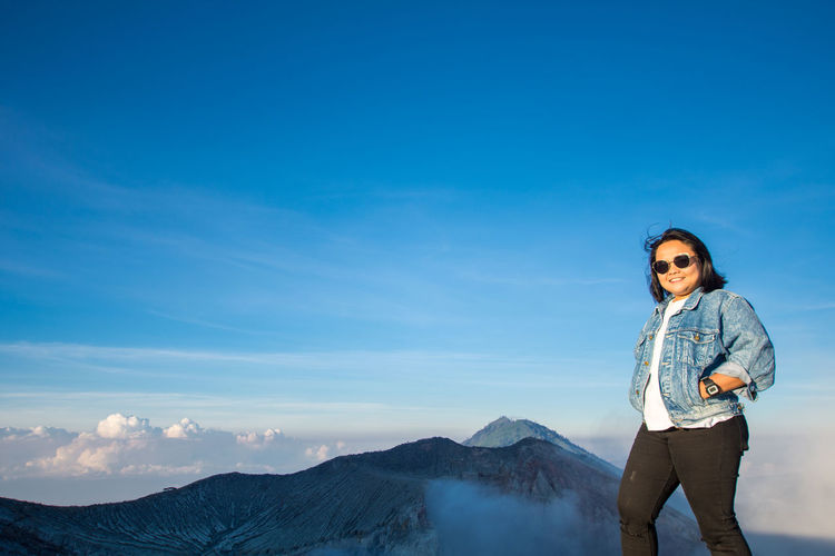 Portrait Of Smiling Woman Standing On Mountain Against Blue Sky