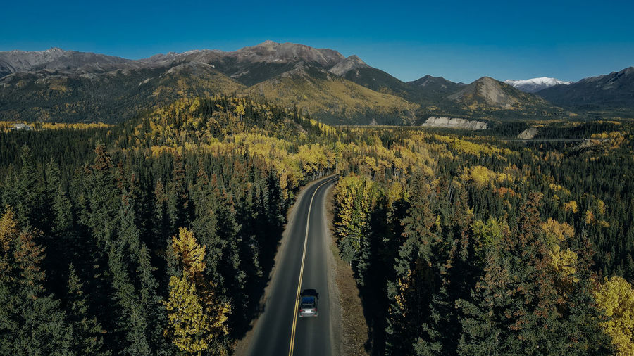 Panoramic shot of road amidst trees and mountains against sky