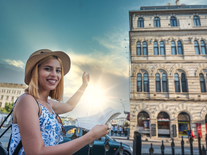 Portrait of smiling woman holding building in city against sky