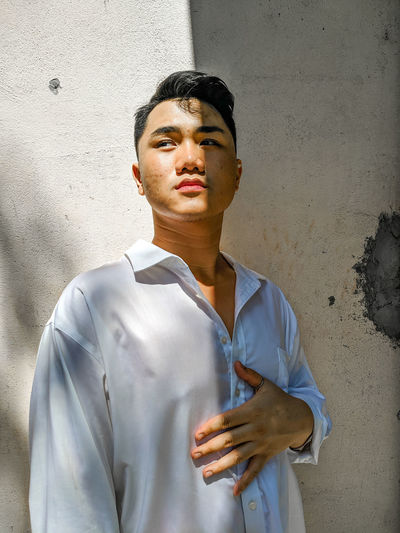 Portrait of young man standing against wall
