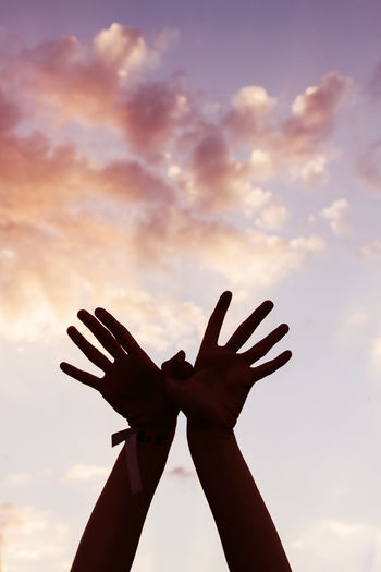 Close-up of silhouette hand against sky during sunset