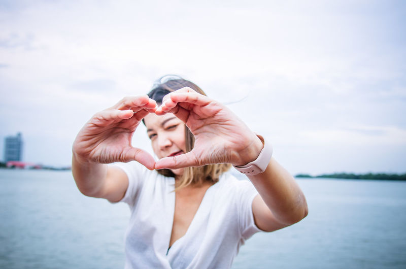 Portrait of woman making heart shape with hands against sea and sky in city
