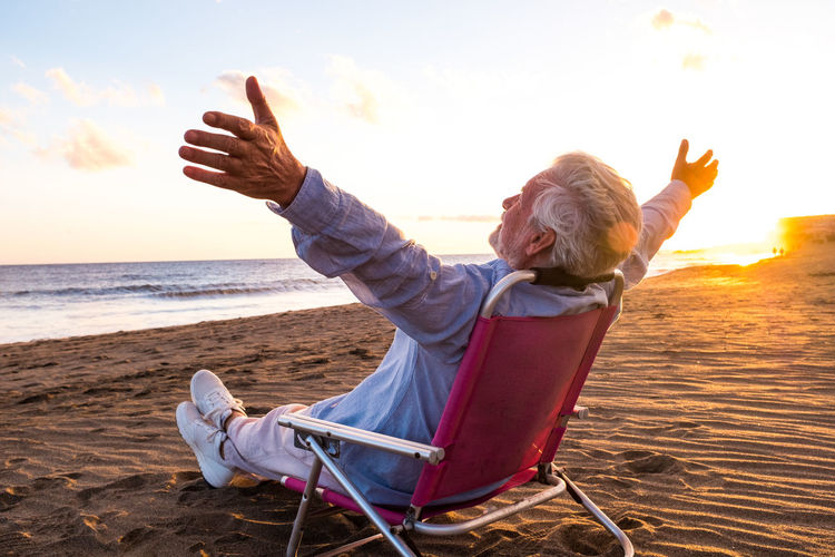 Full length of man sitting on seat at beach against sky