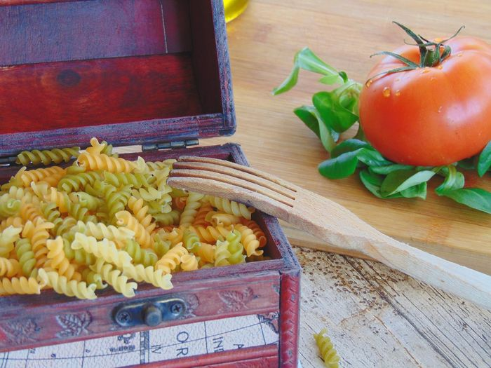 High angle view of pasta in container with vegetables on table
