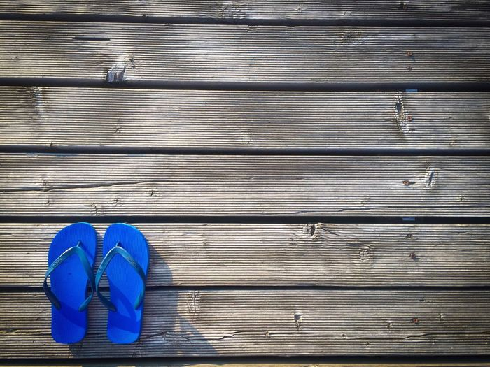 Minimalistic view of blue flip flops in the corner of a wooden pontoon Wood - Material Directly Above High Angle View Blue No People Day Wood Paneling Outdoors Close-up Summer Beach Flipflops Shoes Pontoon Deck Rustic Wooden Minimal Minimalism Minimalistic