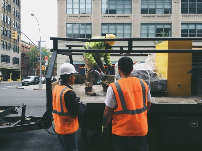 Construction Workers Standing By Truck On Street In City