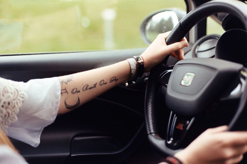 Tattoo Human Hand Hand Mode Of Transportation Transportation Human Body Part Car Motor Vehicle Day Focus On Foreground Communication Real People Adult One Person Steering Wheel Close-up Vehicle Interior Lifestyles Finger Holding Car Interior