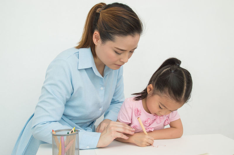 Women Child Childhood Females Indoors  Girls Family Togetherness Family With One Child Front View Mother Headshot Bonding Daughter Parent Table Innocence