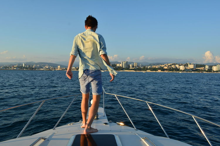 Rear view of young man on sailboat sailing in sea against sky
