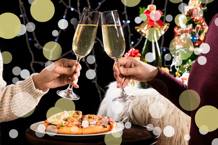 Cropped hands of couple toasting champagne flutes