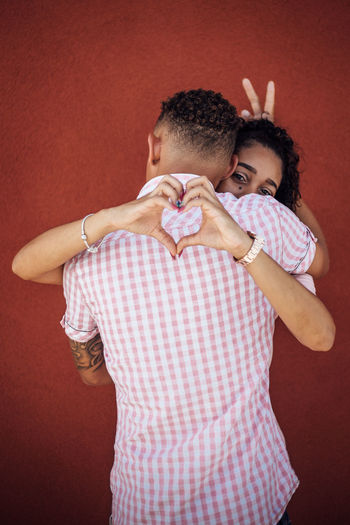 Couple Gesturing While Embracing While Standing Against Red Wall