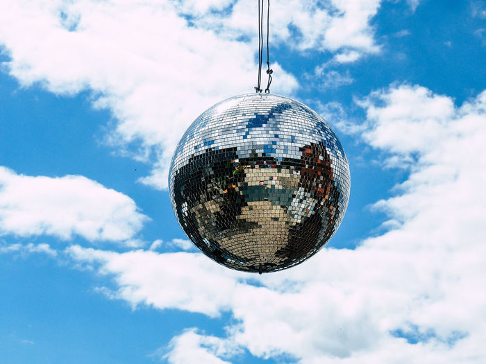 Low angle view of disco ball hanging against sky