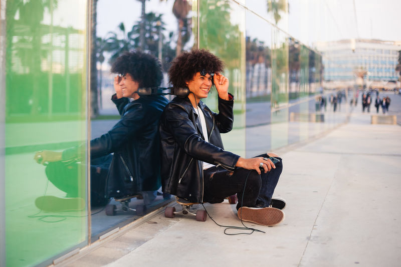 Young couple sitting on glass in city