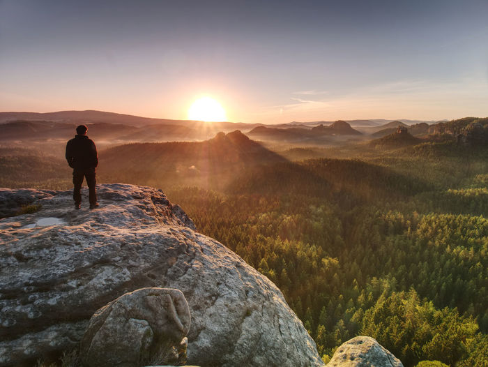 Man on the rock empire with hands in trousers pocket watch over the misty morning valley to sun
