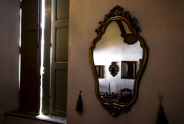 Mirror Image and Window in a Retro Room. Antique Architecture Creativity Light Mirror Mirror Image Old-fashioned Reflection Retro Sunlight Wall Built Structure Decoration Frame Indoors  Light Effect No People Old Old Buildings Old House Retro Styled Shutter Window