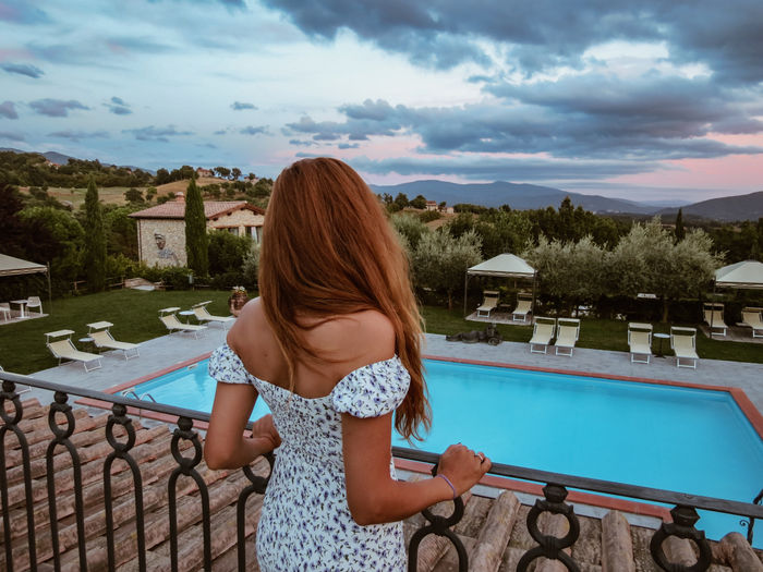 Rear view of woman looking at swimming pool against sky