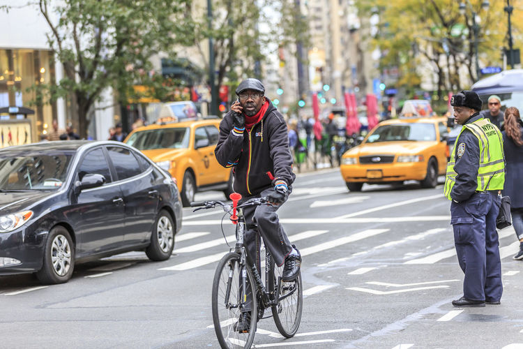 Riding safe with mobile phone in hand. Transportation Mode Of Transportation City Street Bicycle Car Motor Vehicle Architecture Land Vehicle Road Sport Men Real People City Street Helmet Day Riding Ride Full Length One Person Outdoors New York City Phone