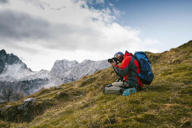Nature photographer with his backpack and equipment taking a photograph Adults Only Autumn Adventure Alps Autumn🍁🍁🍁 Backpack Beauty In Nature Day Equipment Full Length Hiking Leisure Activity Lifestyles Men Mountain Mountain Range Nature Outdoors Photographer In The Shot Real People Scenics Sky