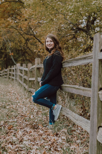 Portrait of smiling young woman standing by railing during autumn