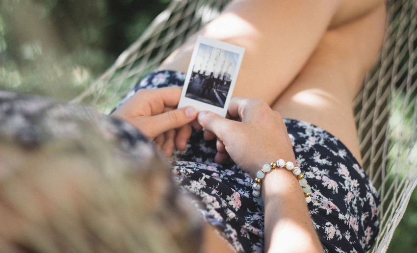 girl lying in hammock holding an instant photo One Person Holding Women Selective Focus Real People Leisure Activity Midsection Day Lifestyles Outdoors Adult Nature Human Hand Close-up Communication Photography Themes Technology Human Body Part Relaxation Instax Polaroid Instant Camera Hammock