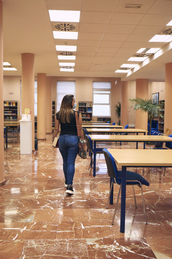 Girl with mask and backpack enters an empty library