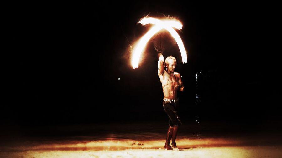 Full length of shirtless man standing at night