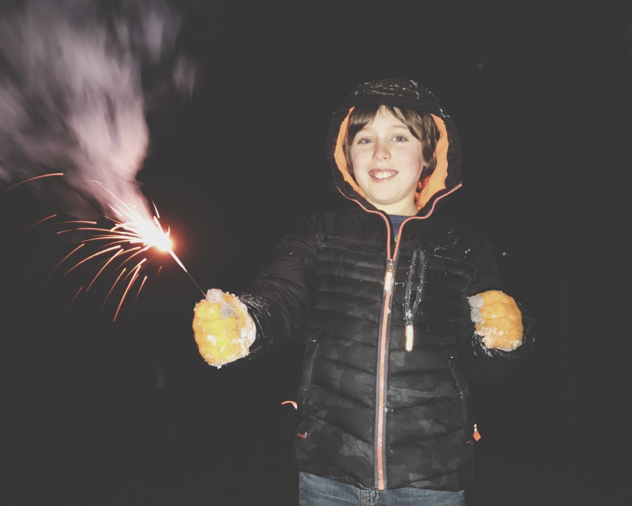 night, front view, one person, standing, sparkler, real people, illuminated, leisure activity, happiness, casual clothing, long exposure, lifestyles, childhood, young women, outdoors, smiling, young adult, black background, motion, looking at camera, portrait, sky, people