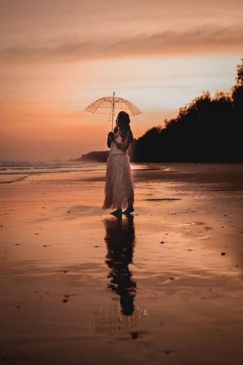 Full length of woman standing on shore against sky during sunset