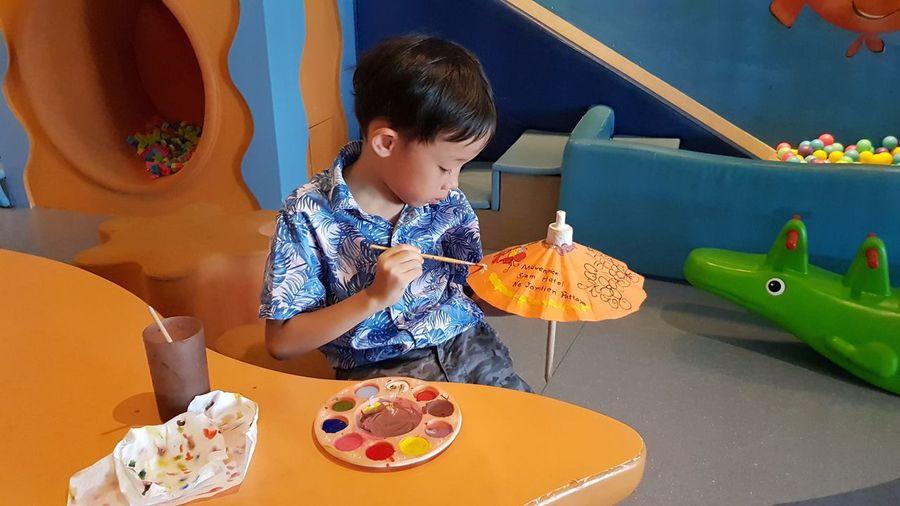Boy painting small umbrella at table