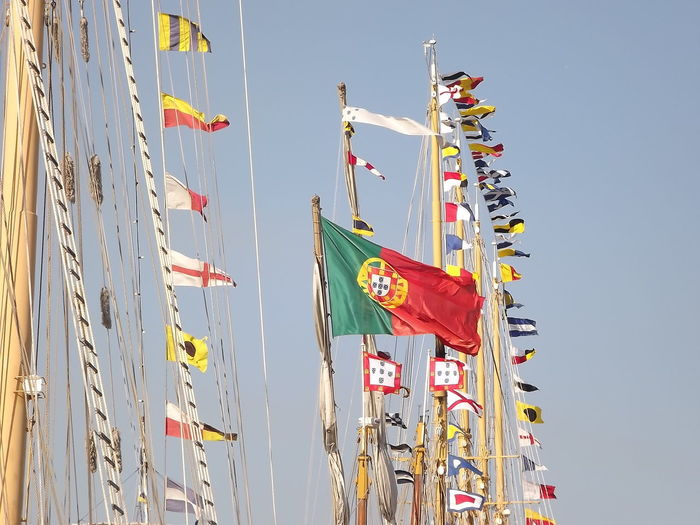 Low Angle View Of Portuguese Flag On Mast Against Sky