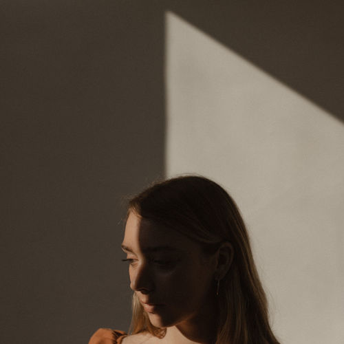 Portrait of young woman looking away against wall