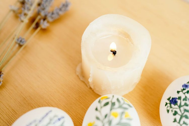 High angle view of lit candles on table